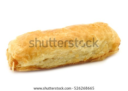 "puff pastry rolls called ""banketstaaf"" with almond paste on a white background"
