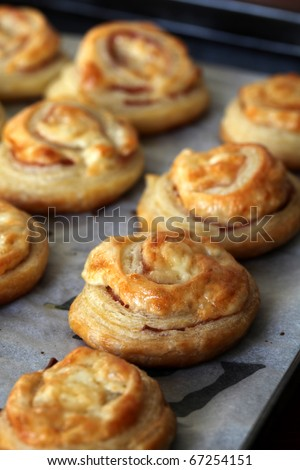 Puff pastry rolls with ham, salami and cheese. Selective focus, shallow DOF - stock photo