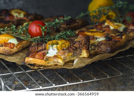 Puff pastry tartlets filled with bacon, mushrooms, chorizo, pepper and quail eggs - stock photo