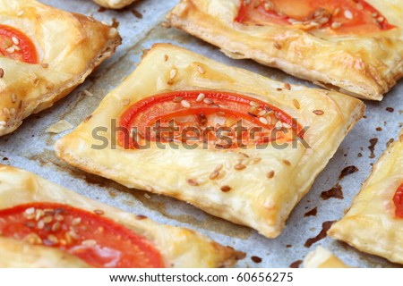 Puff pastry with cheese and tomatoes seasoned with sesame seeds - stock photo