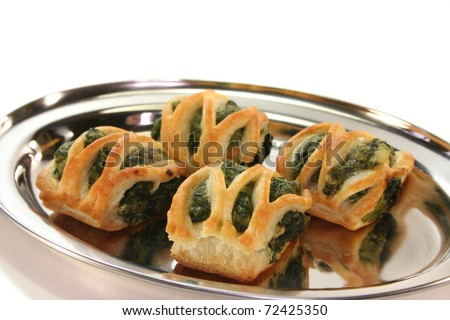 Puff pastry with spinach and cheese filling on a silver tray - stock photo