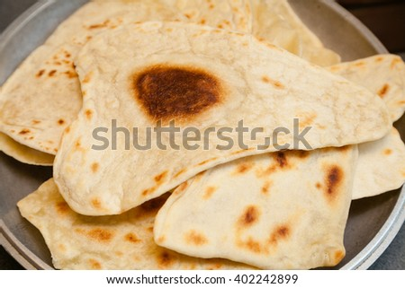 Puffed Indian bread puri on frying pan - stock photo