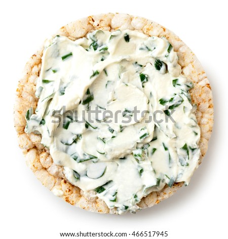 Puffed rice cake with chive and herb spread isolated on white from above.