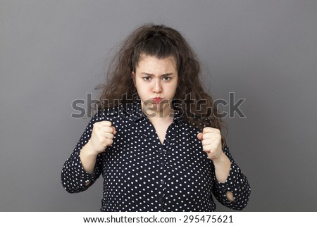 puffing overweight 20's woman expressing exasperation and frustration with both fists and mouth ready to explode - stock photo
