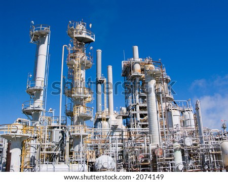 puffs of polluting smoke from a petrochemical plant are barely visible against deep blue sky - stock photo