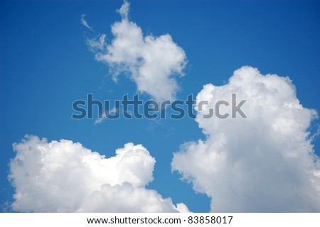 Puffy clouds in a blue sky - stock photo