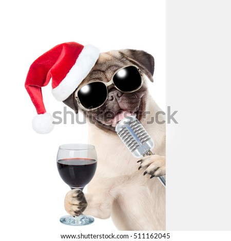Pug puppy with wineglass and retro microphone in red christmas hat peeking from behind empty board. isolated on white background