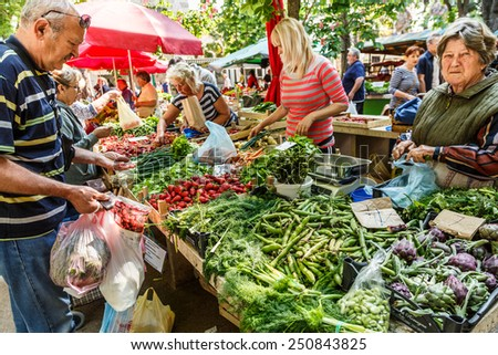 PULA, CROATIA - MAY 11, 2014: merchants sell fruits and vegetables in market stall on May 11, 2014 in Pula, Croatia - stock photo