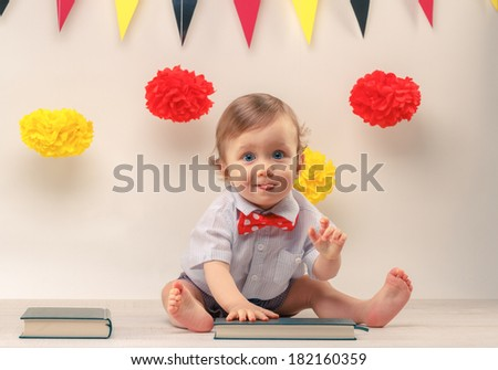 Pull faces cute baby boy looking straight ahead with little tongue out, sitting next to party flags - stock photo