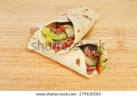 Pulled pork and salad bread wraps on a wooden board - stock photo