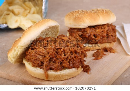 Pulled pork barbecue sandwiches on cutting board - stock photo