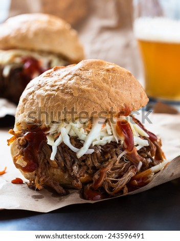 Pulled pork sandwich with cabbage slaw on top served on paper - stock photo