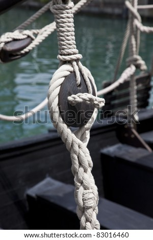 Pulley block on an old wooden sail boat with ropes - stock photo