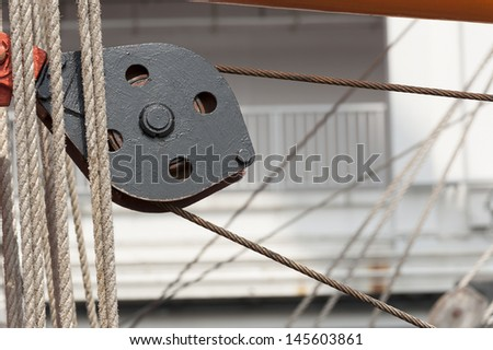 Pulley with ropes on deck - stock photo