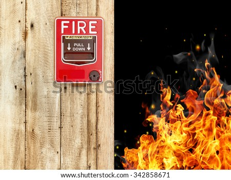 pulling fire alarm on the wall next to the door - stock photo