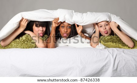 Pulling funny faces with tongues out at sleepover party for three happy beautiful teenage girl friends, a mixed race african american, oriental Japanese and blonde caucasian school mates. - stock photo