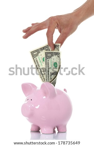 Pulling money from  your savings piggy bank a few dollars at a time angle view - stock photo