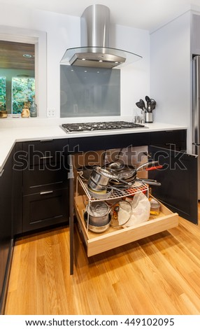 Pullout storage drawer for pots and pans underneath the cooktop - stock photo