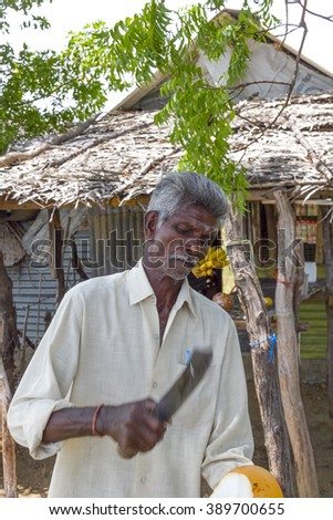 PULMODDAI SRI LANKA - CIRCA 2013 - Unidentified man demonstrates how he skillfully transforms a raw coconut into a drinking vessel with a straw.