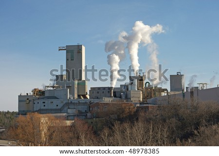 Pulp and paper mill pumping out pollution into the air. - stock photo