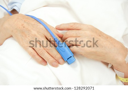 Pulse oxymeter at finger tip - stock photo