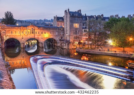 Pulteney Bridge and weir Bath England at twilight.It was designed by Robert Adam and completed in 1773. It is one of only four bridges in the world with shops across the full span on both sides.
