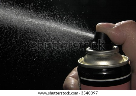 Pulverizing liquid with spray can - stock photo