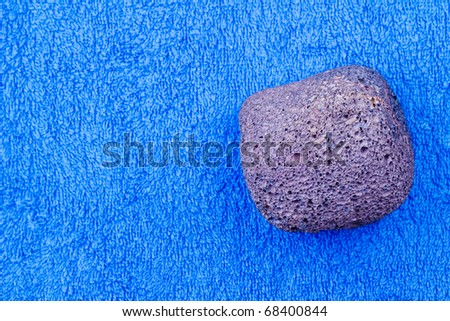 Pumice stone over a towel  isolated on white - stock photo