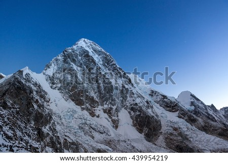Pumori mountain peak on the famous Everest Base Camp trek in Himalayas, Nepal. Snowy mountain summit in the early morning with clear sky. Beautiful mountain peak landscape in Himalayas. - stock photo