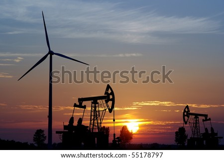pump and wind turbine on sunset background - stock photo