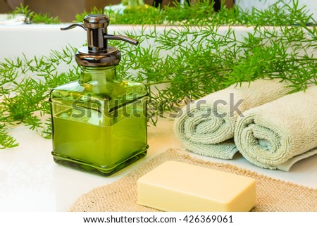 Pump green glass bottle with liquid castile soap. Beige bar soap on burlap. Rolled green towels in a spa setting. Green plant decor in background. Bathroom white countertop.