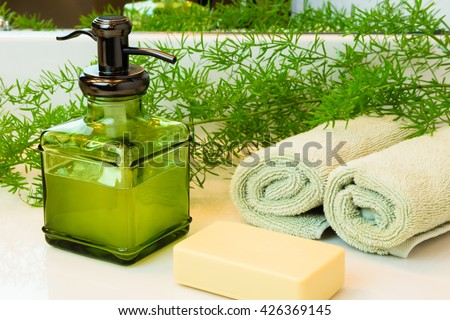 Pump green glass bottle with liquid castile soap. Beige bar soap. Rolled green towels in a spa setting. Green plant decor in background. Bathroom white countertop.
