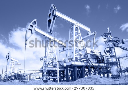 Pump jack and wellhead with valve armature. Extraction of oil.