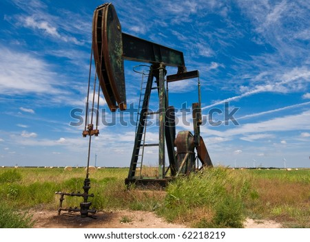 Pump-jack in front of power mills - stock photo