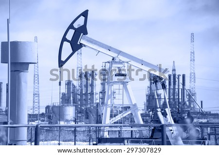 Pump jack on a background of petrochemical plant. Oil and gas industry. Toned.