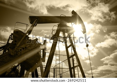 Pump jack on a sky and sun background. Extraction of oil. Toned sepia.