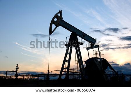 Pump-jack on the sunset sky background. - stock photo