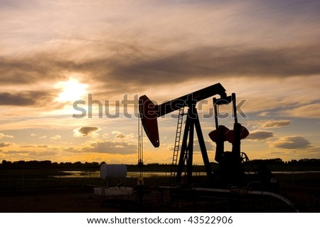 Pump Jack Silhouette at Sunset - stock photo