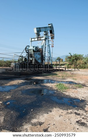 pump jack with crude oil contaminatate to environment - stock photo