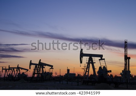 Pump jacks and derrick silhouette during sunset on the oilfield. Oil and gas concept.  - stock photo