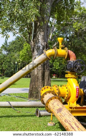 Pump to water pipe yellow in the park.