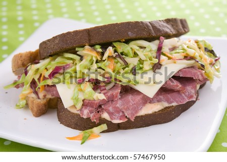 Pumpernickel rye bread filled with thick slices of corned beef, creamy coleslaw, swiss cheese, and thousand island dressing. - stock photo