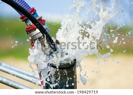 Pumping air from compressor into from new constructed water bore or well as process of cleaning and filtrating water. - stock photo