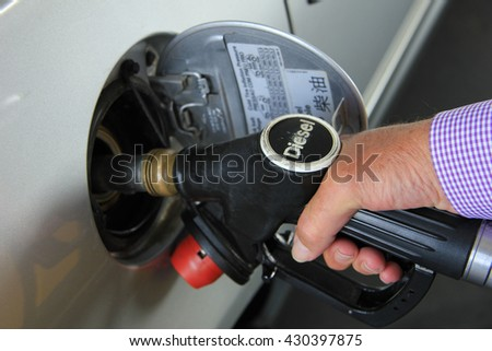 Pumping gas at a self service gas station (Diesel is a type of fuel) - stock photo