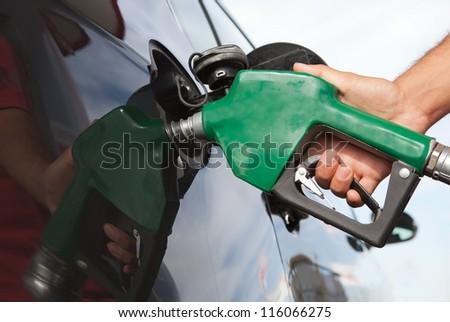 Pumping gas at gas pump. - stock photo
