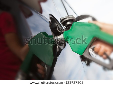 Pumping gas at gas pump - stock photo