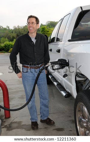 Pumping Gas into a gas guzzling truck.  Why is this man happy?
