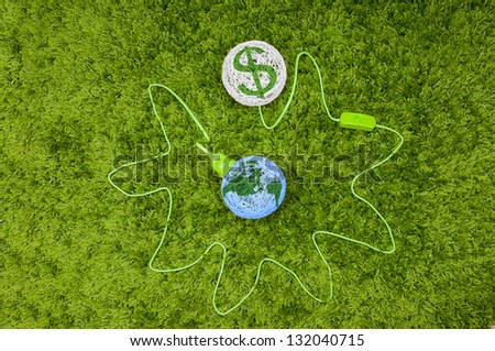 Pumping money from the world. Made of thread balls connected by green wire, on the green carpet. - stock photo