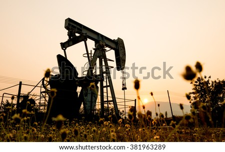 pumpjack at an oil drilling site and sunset - stock photo