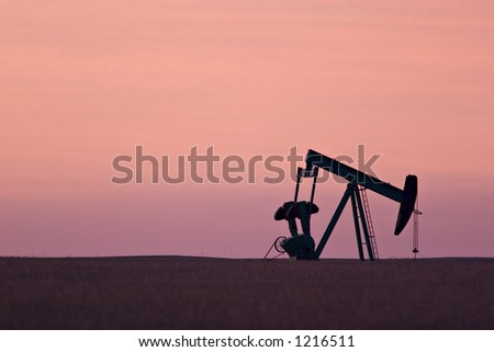 Pumpjack (for oil) at dawn - stock photo